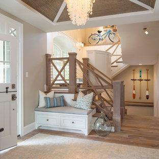 Inspiration för mellanstora maritima foajéer, med mellanmörkt trägolv, en tvådelad stalldörr, beige väggar och en vit dörr