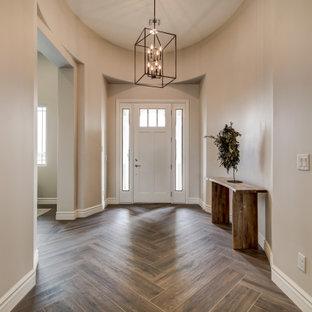 Aménagement d'une grand porte d'entrée avec un mur beige, une porte simple, une porte blanche, un sol marron et un plafond voûté.