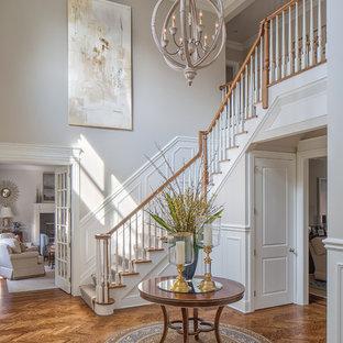 他の地域の大きいトラディショナルスタイルのおしゃれな玄関ロビー (グレーの壁、無垢フローリング、茶色い床、木目調のドア) の写真