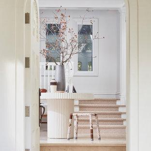 サンフランシスコの広い片開きドアトラディショナルスタイルのおしゃれな玄関ロビー (白い壁、トラバーチンの床、白いドア、ベージュの床、格子天井) の写真