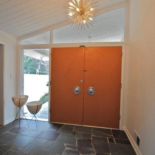 Ispirazione per un ingresso moderno di medie dimensioni con pareti bianche, pavimento in ardesia, una porta a due ante e una porta arancione