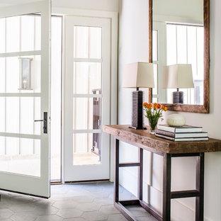 アトランタの片開きドアカントリー風おしゃれな玄関ロビー (白い壁、ガラスドア、グレーの床) の写真