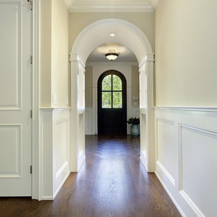 Diseño de hall tradicional, de tamaño medio, con paredes beige, puerta simple, suelo de madera en tonos medios y puerta de madera oscura
