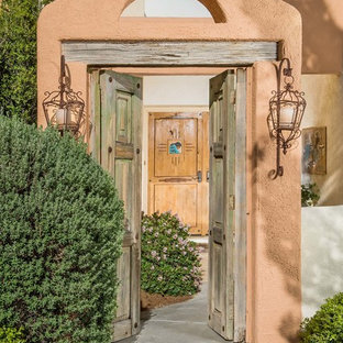 Example of a tuscan entryway design in Austin with orange walls and a medium wood front door