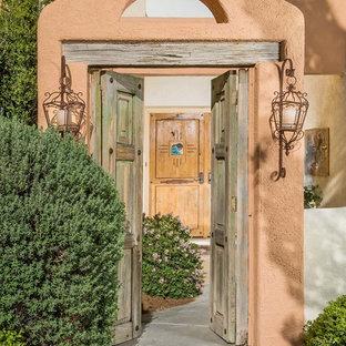 Пример оригинального дизайна: входная дверь в средиземноморском стиле с оранжевыми стенами, двустворчатой входной дверью и входной дверью из дерева среднего тона