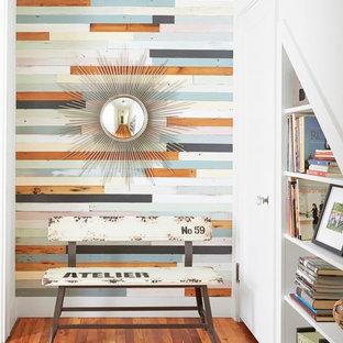 Immagine di un ingresso o corridoio contemporaneo con pareti multicolore, pavimento in legno massello medio, una porta singola e una porta bianca