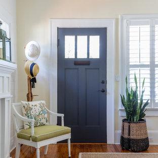 Bild på en shabby chic-inspirerad foajé, med gula väggar, mellanmörkt trägolv, en enkeldörr och en blå dörr