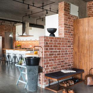 Foto på en industriell foajé, med röda väggar, betonggolv och grått golv