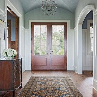 Imagen de distribuidor clásico, grande, con paredes azules, suelo de madera en tonos medios, puerta doble y puerta de madera en tonos medios