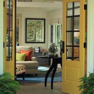 Ispirazione per una porta d'ingresso costiera di medie dimensioni con pareti bianche, pavimento in legno massello medio, una porta a due ante e una porta gialla