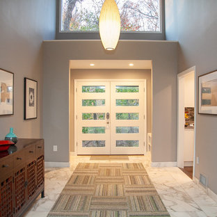 Inspiration for a mid-sized contemporary marble floor and white floor entryway remodel in New York with a white front door and gray walls