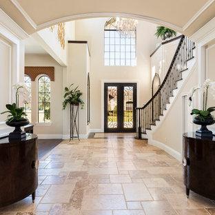 オーランドの広い両開きドアトラディショナルスタイルのおしゃれな玄関ロビー (ベージュの壁、濃色木目調のドア、ベージュの床、ライムストーンの床) の写真