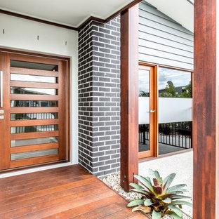 Contemporary front door in Sunshine Coast with a single front door and a medium wood front door.