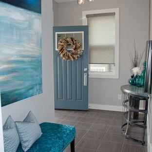 Exemple d'un hall d'entrée moderne de taille moyenne avec un mur gris, un sol en carrelage de porcelaine, une porte pivot et une porte bleue.