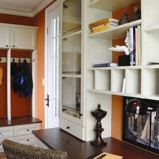 Example of a mid-sized classic dark wood floor mudroom design in New York with orange walls