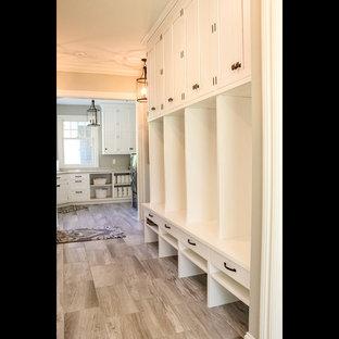 グランドラピッズの大きいビーチスタイルのおしゃれなマッドルーム (グレーの壁、セラミックタイルの床、白いドア、茶色い床) の写真