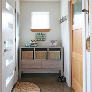 Example of a small transitional concrete floor entryway design in Seattle with white walls and a white front door