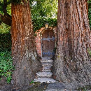 Immagine di un ingresso o corridoio bohémian con una porta singola e una porta in legno scuro