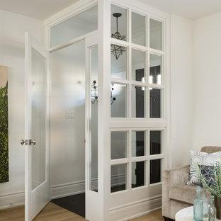 トロントの小さい片開きドアトランジショナルスタイルのおしゃれな玄関ラウンジ (白い壁、御影石の床、濃色木目調のドア) の写真