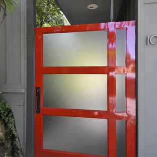 Esempio di una porta d'ingresso contemporanea con una porta a pivot, una porta rossa e pareti grigie