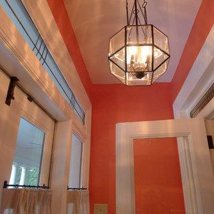 Esempio di un grande ingresso con vestibolo chic con pareti arancioni, una porta a due ante e una porta bianca