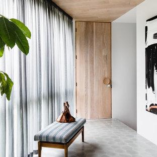 Bild på en funkis foajé, med vita väggar, klinkergolv i keramik, en enkeldörr, ljus trädörr och grått golv