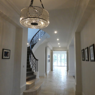 メルボルンの巨大な両開きドアトランジショナルスタイルのおしゃれな玄関ホール (白い壁、トラバーチンの床、濃色木目調のドア) の写真