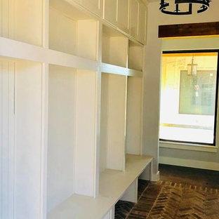 Idéer för mellanstora lantliga kapprum, med vita väggar, tegelgolv och brunt golv