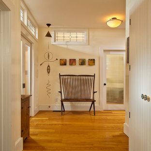 Entry hall - cottage medium tone wood floor entry hall idea in New York with beige walls