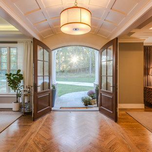Exemple d'un hall d'entrée craftsman de taille moyenne avec un mur gris, un sol en bois brun, une porte double, une porte en bois brun, un plafond voûté et du lambris.