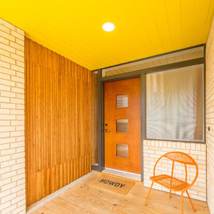 Mid-sized mid-century modern plywood floor entryway photo in Austin with multicolored walls and a medium wood front door