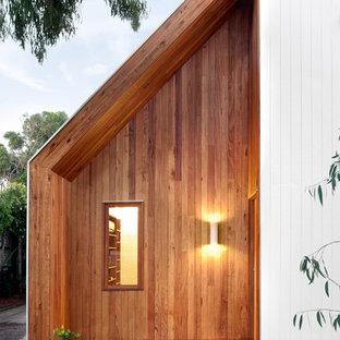 Idée de décoration pour une porte d'entrée design avec une porte orange.