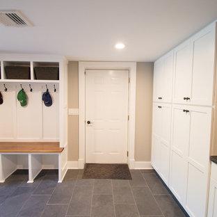 Klassisk inredning av ett stort kapprum, med beige väggar, skiffergolv, en enkeldörr och en vit dörr