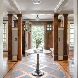 Пример оригинального дизайна: фойе в классическом стиле с серыми стенами, паркетным полом среднего тона, одностворчатой входной дверью, входной дверью из дерева среднего тона, коричневым полом и балками на потолке