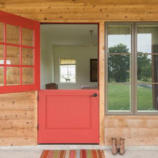 Bild på en lantlig ingång och ytterdörr, med en tvådelad stalldörr och en röd dörr