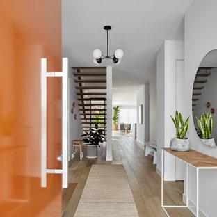 Неиссякаемый источник вдохновения для домашнего уюта: узкая прихожая в современном стиле с белыми стенами, одностворчатой входной дверью, оранжевой входной дверью, коричневым полом и светлым паркетным полом