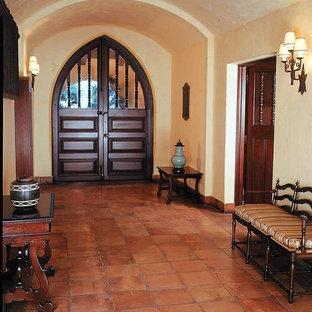 Foto di una grande porta d'ingresso mediterranea con pareti beige, pavimento in terracotta, una porta a due ante, una porta in legno scuro e pavimento marrone
