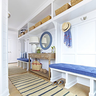 Example of a mid-sized coastal light wood floor mudroom design in New York with white walls
