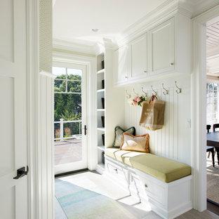 Réalisation d'une grand entrée marine avec un vestiaire, un mur vert, un sol en carrelage de céramique, une porte simple, un sol gris et une porte en verre.