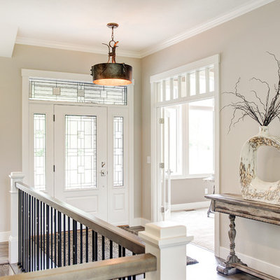 Example of a mid-sized transitional medium tone wood floor entryway design in Other with beige walls and a white front door
