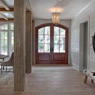 Idée de décoration pour un grand hall d'entrée ethnique avec un mur blanc, un sol en bois brun, une porte double et une porte en verre.