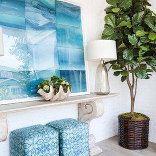Idées déco pour un petit hall d'entrée bord de mer avec un mur blanc et un sol en bois clair.