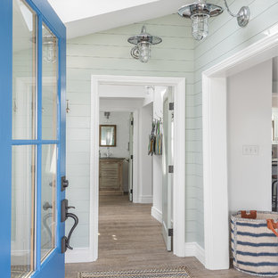 Example of a coastal light wood floor entryway design in Portland Maine with blue walls and a blue front door