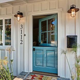 Inspiration för en mellanstor maritim ingång och ytterdörr, med en tvådelad stalldörr, en blå dörr, vita väggar och kalkstensgolv