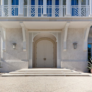 Island style entryway photo in Miami with a white front door