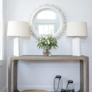 Inspiration for a mid-sized coastal medium tone wood floor and brown floor entryway remodel in New York with white walls and a white front door