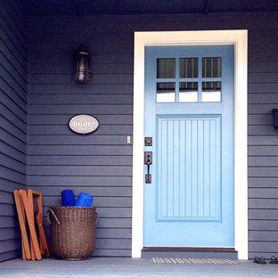 На фото: входная дверь среднего размера в морском стиле с синими стенами, бетонным полом, одностворчатой входной дверью и синей входной дверью с