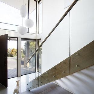 Ejemplo de distribuidor costero, grande, con paredes blancas, puerta simple, suelo de baldosas de porcelana y puerta marrón