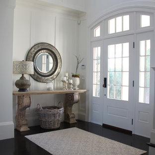 Aménagement d'une entrée bord de mer avec un sol en bois foncé, une porte simple et une porte blanche.