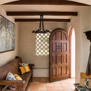 ロサンゼルスの中くらいの片開きドア地中海スタイルのおしゃれなマッドルーム (ベージュの壁、テラコッタタイルの床、濃色木目調のドア) の写真